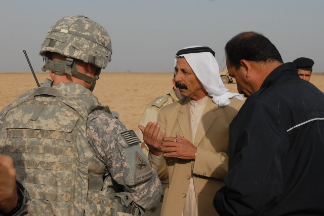 "Lt. Col. Andy Shoffner, of Harker Heights, Texas, the commander of 4th Squadron, 9th Cavalry Regiment, 2nd Brigade Combat Team, 1st Cavalry Division, and Iraqi Police Brig. Gen. Sarhad, the police chief for the rural areas in the region, speak with a local Sheikh during operation ""Dark Horse Cossack Two"" March 15. Shoffner and Sarhad questioned the Sheikh concerning insurgents in the area."