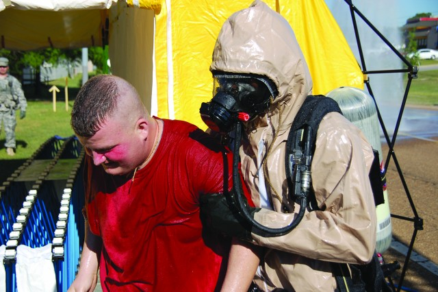 """A Fort Polk firefighter takes a """"casualty"""" from a decontamination tent to an ambulance during an emergency operations exercise March 18. The event gave the post organizations and leadership an opportunity to test their response to a terrorist attack. See pages 16-17 of today's Guardian for full story and more photos."""