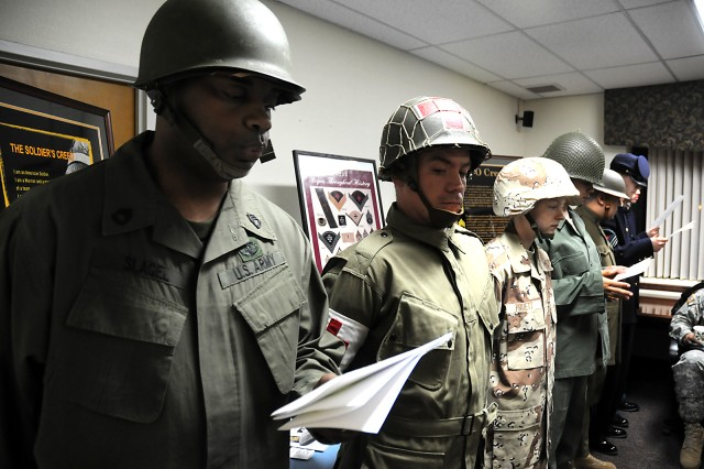 Sgt. Marques Washington reads a portion of the proclamation establishing the Army Hospital Service Corps during the corps anniversary presentation March 18 at Munson Army Health Center, Fort Leavenworth, Kan. Washington is wearing a Vietnam era uniform. Other historical uniforms were presented by Sgt. Paul Huston in World War II era, Pfc. Stephanie Foy in Desert Storm era, Spc. Megan Rogers in Korean War era, Spc. Daniel Alarcon in World War I era, Pfc. Nathan Rosemond in Civil War era and Spc. Bo Zhang representing the original hospital steward uniform from the 1880s.