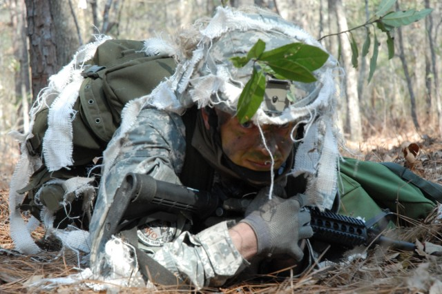 """Staff Sgt. Matthew Knutt, donning full camouflage, low crawls as he demonstrates evasive maneuvers during this week's EIB competition."""""""