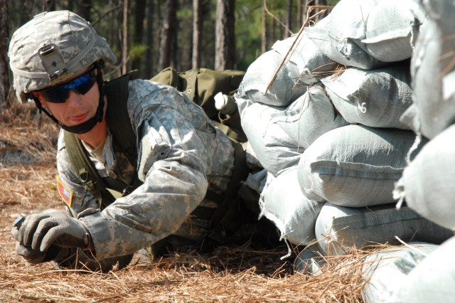 Staff Sgt. Matthew Knutt throws a hand grenade into a foxhole during one portion of the EIB hand grenade station.