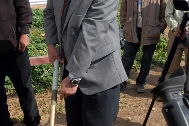 Jim Vancura, the senior agricultural advisor for Forward Operating Base Warrior's Provincial Reconstruction Team, strikes dirt with a golden shovel symbolizing the start of renovations and construction at the Kirkuk grain silo, Kirkuk city, Iraq, March 10.