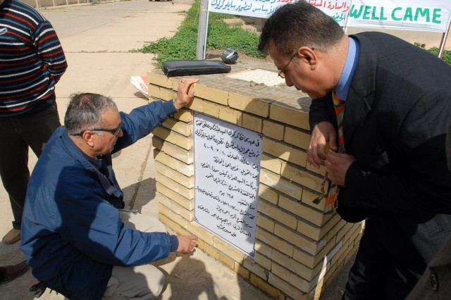 Visitors read a plaque commemorating the start of renovations at the Kirkuk grain silo in downtown Kirkuk city, Iraq, March 10.