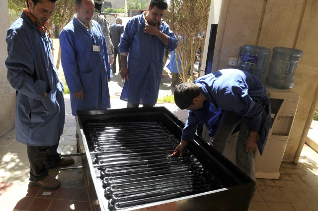 BAGHDAD - Former Sons of Iraq members work on a solar-powered device used to heat water while attending a Demobilization, Demilitarization and Reintegration Center in western Adhamiyah March 12.  This machine will enable Iraqi families to have hot water in their homes.