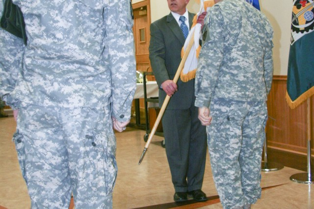U.S. Army Sustainment Command's Commanding General, Maj. Gen. Robert M. Radin, presents the Senior Executive Service flag to Carl Cartwright during a ceremony March 27, at Heritage Hall on Rock Island Arsenal. Cartwright works for the ASC as the command's Executive Director for Field Support.