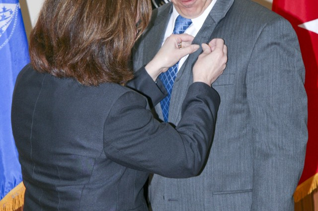 Carl Cartwright is pinned by his wife, Barbara, with the Senior Executive Service lapel pin during a ceremony March 27, at Heritage Hall on Rock Island Arsenal. Cartwright works for the U.S. Army Sustainment Command as the command's Executive Director for Field Support.