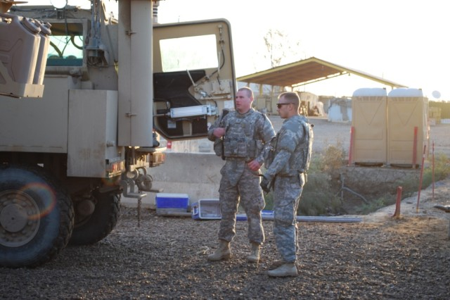 CAMP TAJI, Iraq - Spc. Joshua Pastir (right) and Pfc. Jeremiah Pomerleau (left), Soldiers from 3rd Platoon, 62nd Engineer Company, 4th Engineer Battalion, 225th Engineer Brigade, discuss their vehicle's load plan while conducting pre-combat checks prior to the start of their March 21 route clearance patrol.