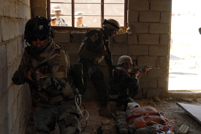 """BAGHDAD - Soldiers of 6th Iraqi Army Division pull security in a cleared room during a training exercise at Joint Security Station Salam while members of the 6th IA Div. Military Transition Team observe. """"We want them to sustain what the American Soldiers have trained them to do. When we leave out, they should be able to do this on their own,"""" said Sgt. 1st Class Preston Grant, Karkh Area Command liaison, 6th IA Div. MiTT."""