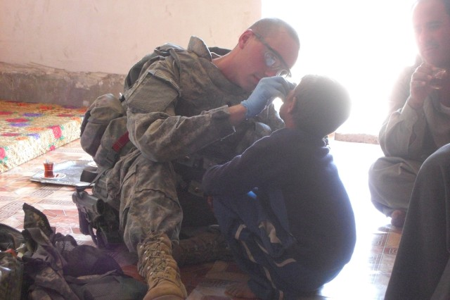TAJI, Iraq - Spc. Neal Cooper, a medic with Troop A, 2nd Squadron, 104th Cavalry Regiment, who hails from Myerstown, Pa., cleans out an abnormal cyst on the face of a young Iraqi child March 20. In an area where medical assistance is a rarity, Cooper's work is never done.