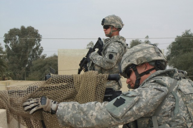 TAJI, Iraq - Sgt. Robert Lower (front), from White Haven, Pa., and Pfc. Cody Venesky, from Peckville, Pa., both in Headquarters and Headquarters Troop, 2nd Battalion, 104th Cavalry Squadron, 56th Stryker Brigade Combat Team, perform security from the roof of a local government building March 11 while local leaders conduct a meeting inside.