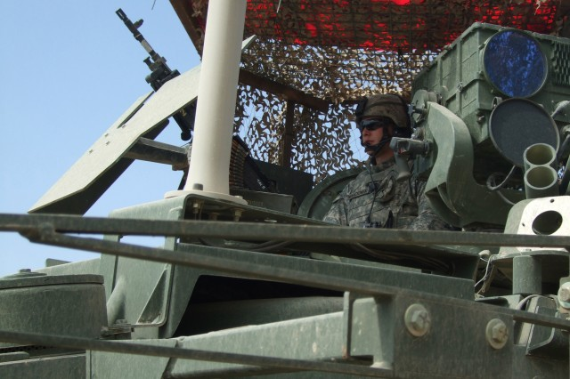 TAJI, Iraq - Spc. Alphonso Novackowski, from Kingston Pa., with Headquarters and Headquarters Troop, 2nd Battalion, 104th Cavalry Squadron, 56th Stryker Brigade Combat Team, stands guard in the commander's hatch of his Stryker vehicle during a local government meeting in the Taji area of Iraq March 11.