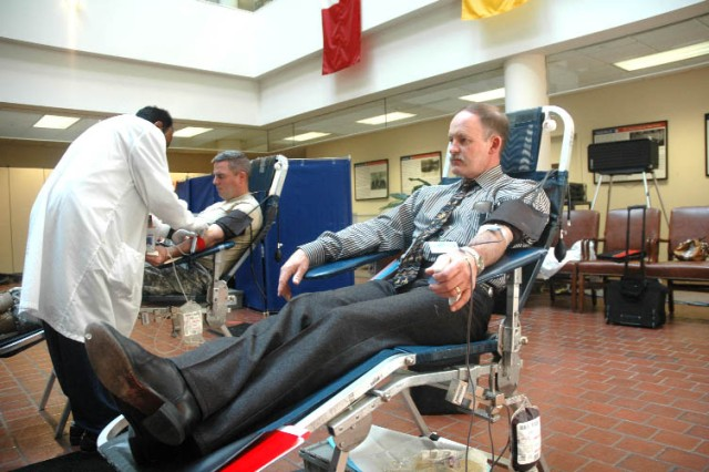 FORT MCPHERSON, Ga. -- Royce Rhoades, the organizational management branch chief of G3 for U.S. Army Forces Command(right), finishes his donation of blood while Seman Fedil, Red Cross mobile blood lab technician (left), prepares Maj. Mike Doyle, an operation research systems analyst for G3 FORSCOM, for his donation Monday at FORSCOM headquarters.  The American Red Cross exceeded its goal of 25 pints donated in the drive.