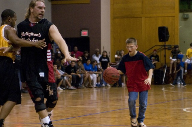 ALIAMANU MILITARY RESERVATION, Hawaii - Michael Black, 11, dribbles down the court as American Gladiator, Wolf, blocks the opposing team. The celebrity basketball game brought family fun and crowd participation as family members joined the game, dribbling, shooting free throws, and passing to Soldiers and celebrities.