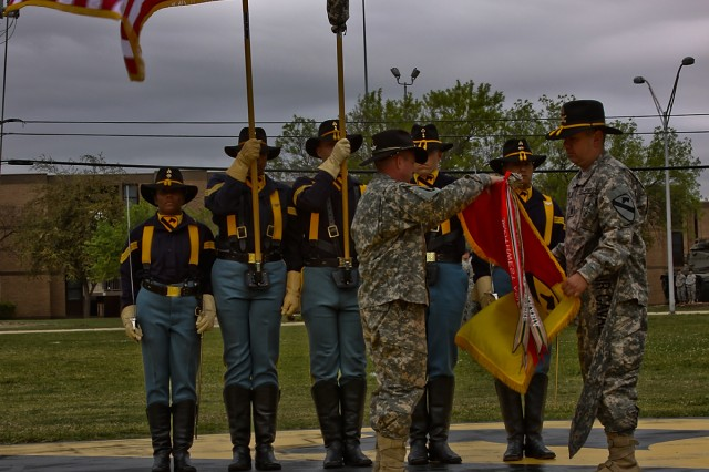 Flanked by the 1st Cavalry Division honor guard, Col. Douglas Gabram (left), from Cleveland, commander, 1st Air Cavalry Brigade, 1st Cavalry Division and Command Sgt. Maj. Glen Vela (right), from Dallas, command sergeant major, 1st ACB, 1st Cav. Div., case the brigade colors, March 25, at Cooper Field, Fort Hood, Texas, during the 1st ACB's color casing ceremony as they prepare to deploy to Iraq in support of Operation Iraqi Freedom.