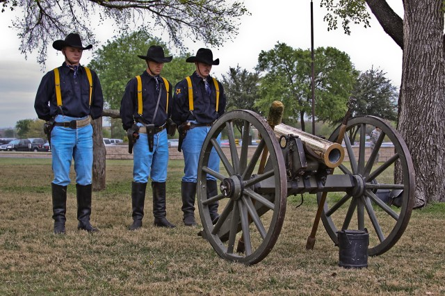 Set to the backdrop of a vintage cannon, three Soldiers from the 1st Cavalry Division horse detachment bow their heads during the invocation delivered by Chaplain (Maj.) Tyson Wood, 1st Air Cavalry Brigade, 1st Cavalry Division, during the 1st ACB color casing ceremony, March 25, at Cooper Field, Fort Hood, Texas.