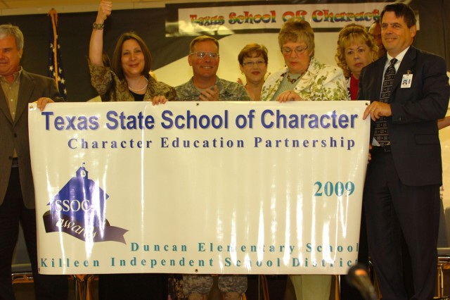 Members of the Killeen Independent School District and III Corps and Fort Hood deputy commander, Brig. Gen. James M. McDonald, hold up the banner that was awarded to Duncan Elementary School for winning the Texas State School of Character award, March 25, on Fort Hood, Texas.