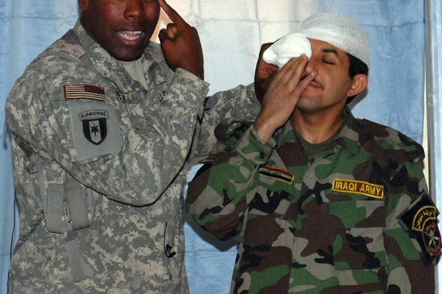BAGHDAD - Sgt. 1st Class Gary Petty (left), division surgeon advisor with the 6th Iraqi Army Division Military Transition Team, explains the treatment of an impaled object in the eye during a March 25 combat lifesaver class.