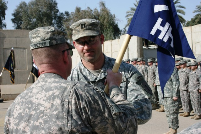 "BAGHDAD - Lt. Col. John Vermeesch (left), a native of Marshall, Mich., commander, 1st Combined Arms Battalion, 18th Infantry Regiment, passes the Headquarters and Headquarters Company guidon to Capt. Clint Olearnick, a native of Parker, Colo., commander, HHC, 1st Bn., 18th Inf. Regt. at Forward Operating Base Justice March 19. The ""Passing of the Guidon"" signifies Olearnick's assuming of his new position as the commander of HHC, 1st Bn., 18th Inf. Regt."