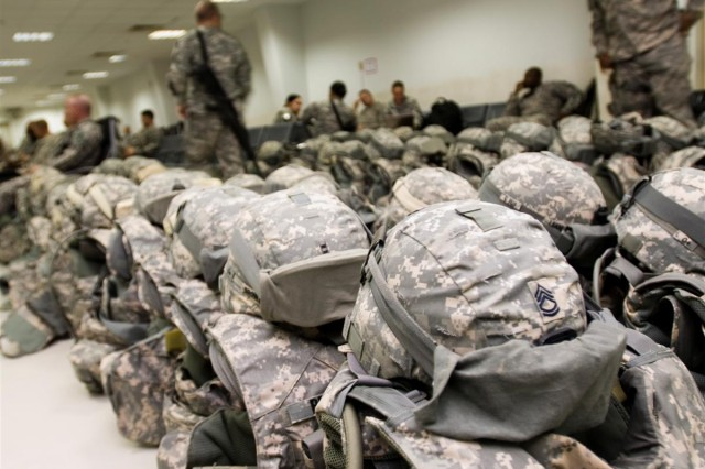 Helmets and body armor belonging to Soldiers of the 100th Brigade Support Battalion from Fort Sill, Okla., are lined up prior to departure at the passenger terminal at Joint Base Balad, Iraq, in preparation for unit's flight to Afghanistan. The 100th BSB, an active-component unit from Fort Sill, Okla., was repositioned from Iraq to Afghanistan on March 28, to provide logistical support to Coalition forces there.