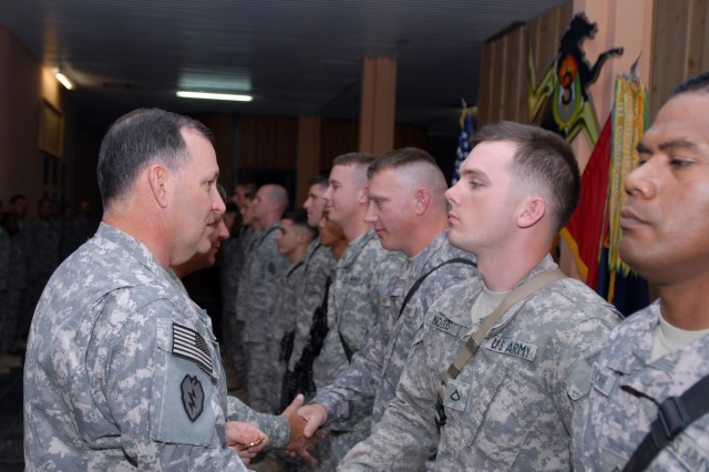 CONTINGENCY OPERATING BASE SPEICHER, TIKRIT, Iraq - Lt. Gen Benjamin Mixon, USARPAC commanding general, shakes the hand of Pfc. Brian Nogues, Battery B, 3rd Battalion, 7th Field Artillery Regiment, 3rd Infantry Brigade Combat Team, 25th Infantry Division March 25. Nogues and his fellow Soldiers were recognized by Mixon for their outstanding duty performance during their deployment