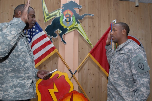 CONTINGENCY OPERATING BASE SPEICHER, TIKRIT, Iraq - Lt. Gen Lloyd Austin, Multi-National Corps-Iraq commanding general, administers the oath of enlistment to Staff Sgt. Clarence Charatain, platoon sergeant, Co. B, 325th Brigade Support Battalion, 3rd Infantry Brigade Combat Team, 25th Infantry Division, during his visit to the Bronco Brigade, March 25.
