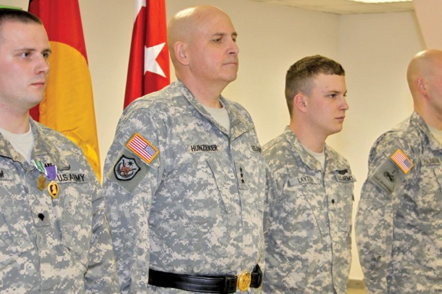 Spc. Tyler Latham, Lt. Gen. Kenneth Hunzeker, Spc. Tanner Layton, Spc. Daniel Hausamann and Spc. Darraivius Strawder stand at attention as citations for Layton's awards are read.