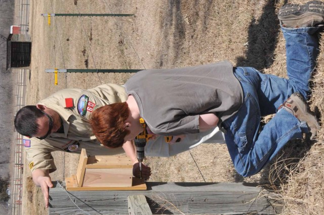 Scout master Vincent VanCleave assists Morgan Ling with putting up his birdhouse on March 17.