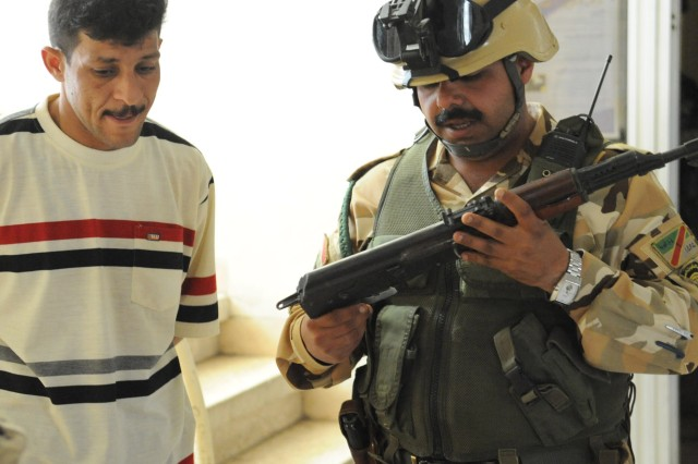 BAGHDAD - A member of the Awakening Council (left) turns in his weapon to an Iraqi Army soldier in the Fadhil neighborhood of eastern Baghdad, March 29. Iraqi Security Forces disarmed the council following two days of sporadic gunfire between the group and the ISF. Violence erupted following the warrant-based arrest of the Fadhil Awakening Council's leader Adil al-Mashhadani.  Supported by U.S. forces, the ISF took to the streets in order to restore peace in the area.