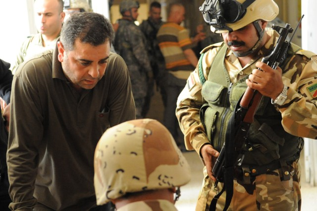 BAGHDAD - A member of the Awakening Council turns in his weapon to an Iraqi Army soldier in the Fadhil neighborhood of eastern Baghdad March 29. Iraqi Security Forces disarmed the council following two days of sporadic gunfire between the group and the ISF. Violence erupted following the warrant-based arrest of the Fadhil Awakening Council's leader Adil al-Mashhadani. ISF took to the streets in order to restore peace in the region. ISF was supported by U.S. forces during the Iraqi-led military operation.