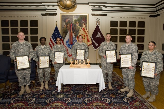 """Seven new inductees into the NCO Corps display their framed NCO Creed following the West Point NCO Induction ceremony on March 27.  Pictured, left-to-right, are Sgts. Nathan Lunsford, Stephanie Denis, Teresa Rivera, Noah Evans, Sameul Vass, Scott Issler and Andrea Thompson. The inductees are the first NCOs inducted into the NCO Corps at West Point this year, which is the """"Year of the Non-commissioned Officer""""."""
