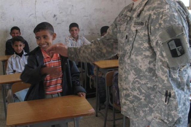 "Lt. Col. Clint Moyer, the 287th Sustainment Brigade Civil Military Operations chief, high-fives a student at Al Nwares Elementary School in Dhi Qar Province, Iraq. Moyer, also a teacher in Clearwater, Kan., gave the class a math pop quiz during his ""Safety First"" visit to teach children about convoy safety on March 11. (U.S. Army photo by Sgt. Heather Wright)"