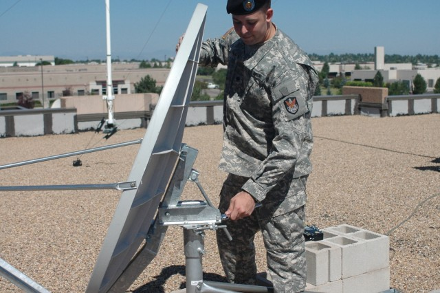 """117th Signal Battalion satellite systems operator/maintainer Spc. David Wilde adjusts a satellite antenna atop a building in Colorado Springs, Colo."""""""