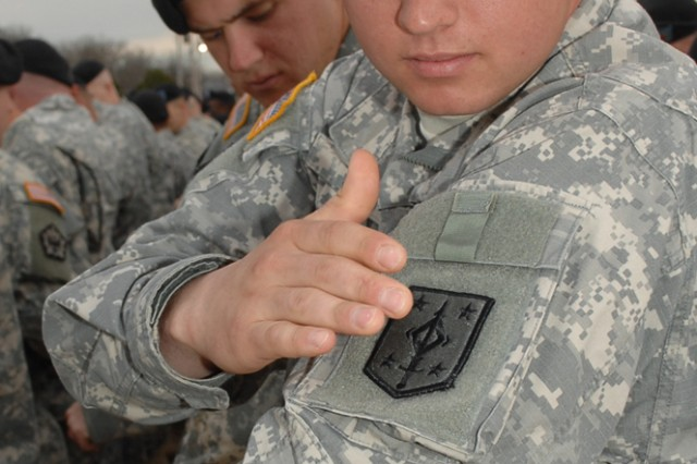 CUTLINE: Spc. Brett Nye, 252nd Engineer Company, places the new 4th MEB unit patch on his uniform during a ceremony at Fort Leonard Wood, Mo., March 23.