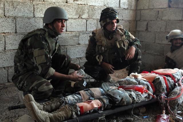 BAGHDAD - Soldiers with the 6th Iraqi Army Division prepare to treat wounds on a medical dummy constructed by Sgt. 1st Class Victor Orozco, Karkh Area Command liaison, 6th IA Div. Military Transition Team. The Fort Carson, Colo. native fitted the dummy with working limbs, a number of areas that bleed and a chest cavity that can be decompressed with a needle. The dummy can also be stabbed, allowing treatment of an impaled object.