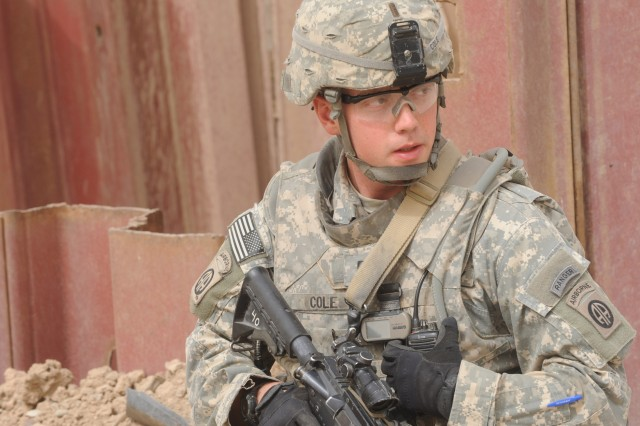 1st Lt. Logan Cole, of Fort Knox, Ky., uses a communication device to relay instructions to his Soldiers during a foot patrol, March 28, in eastern Baghdad.