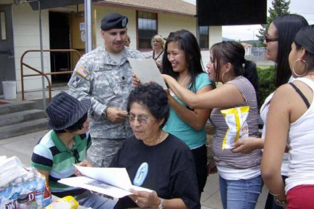 Lt. Col. Adrian Nagel, garrison commander of Camp Navajo, Ariz., and members of the Elfrieda Etsitty Tsosie Family, examine historical documents at the Camp Navajo Reunion July 19, 2007. Camp Navajo's oral history project helped the Arizona National Guard training center win the fiscal 2008 Secretary of the Army Environmental Award for cultural resources management.