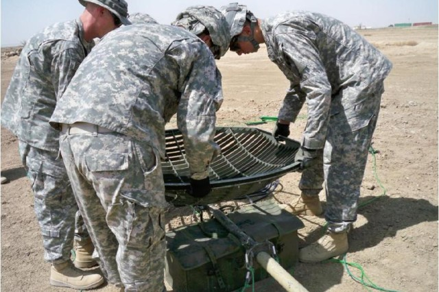 Sgt. Jody Tripp teaches Pfc. Jonathan Josd and Pfc. Mark Cichoracki, Soldiers with the 4th Special Troops Battalion, 4th Brigade Combat Team, 1st Cavalry Division, how to properly install the15M-mast satellite dish to provide optimal coverage for the brigade's network communications system at Contingency Operating Base Adder, Iraq recently.