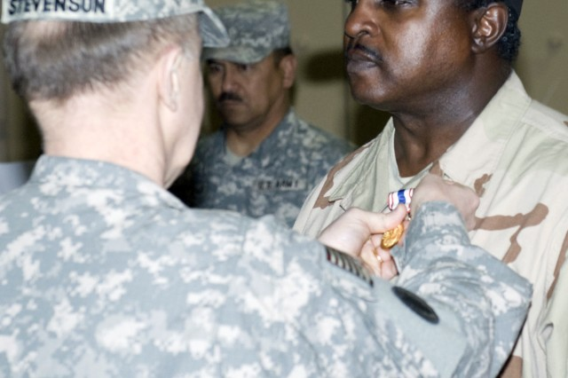 Lt. Gen. Mitchell H. Stevenson, deputy chief of staff for Logistics (G-4), Headquarters, Department of the Army, pins a Defense of Freedom Medal on Tony M. Hall during a ceremony at Joint Base Balad, Iraq, Feb. 18.