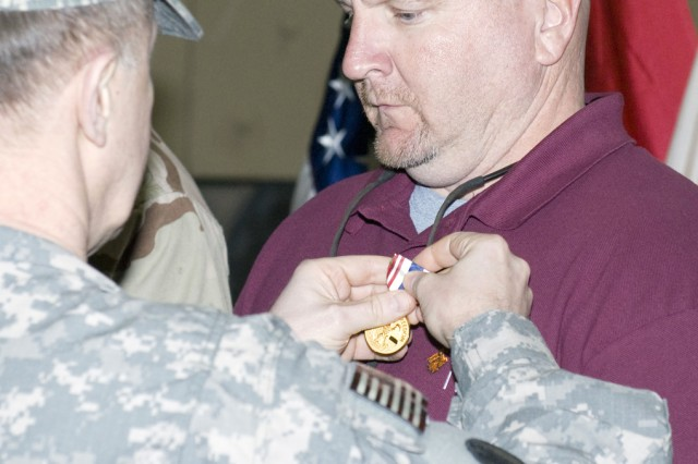 Lt. Gen. Mitchell H. Stevenson, deputy chief of staff for Logistics (G-4), Headquarters, Department of the Army, pins a Defense of Freedom Medal on Christopher Kirby during a ceremony at Joint Base Balad, Iraq, Feb. 18.