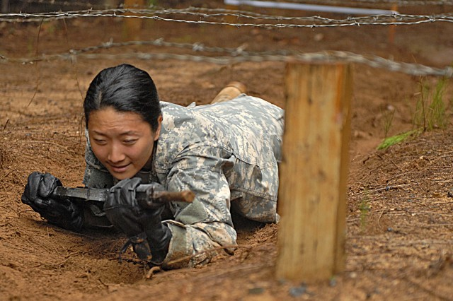 SCHOFIELD BARRACKS, Hawaii - (Mar. 26, 2009) Cpt. Jasmin Cho, U.S. Army, Pacific North Asia Desk Officer, low crawls with a weapon at the East Range Obstacle Course.