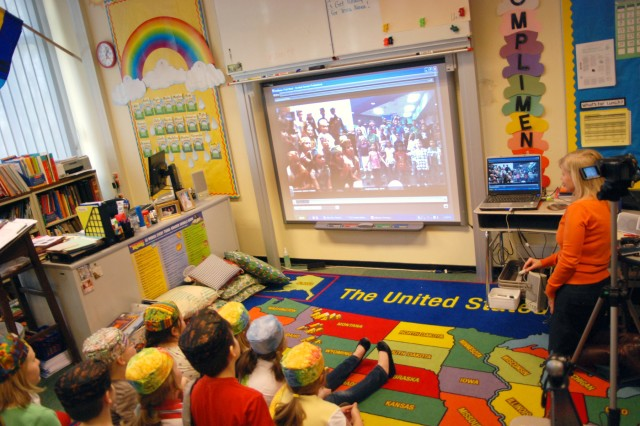 Using a laptop, a Web cam and the classroom whiteboard as a monitor, third-graders at SHAPE Elementary School communicate with students at Meadows Elementary School at Fort Hood, Texas. The Texas students, on the right of the monitor, are singing and dancing for the students in Belgium.