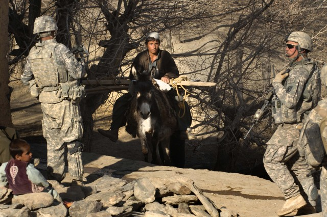 Spc. Daniel Camino, left, and Staff Sgt. Cody Collins, Company A, 2nd Battalion, 87th Infantry Regiment, stop a local boy riding his donkey near a meeting with local leaders in Afghanistan's Jalrez Valley, Wardak province, March 12, 2009. The patrol secures the area for the meeting and is watchful of attacks in one of the most dangerous valleys in the province.
