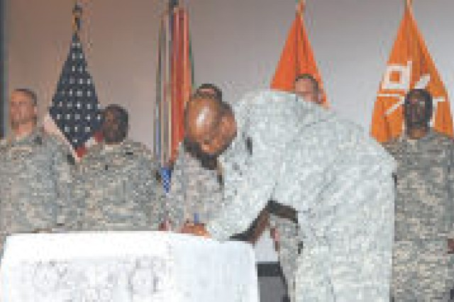 Warrior Transition Battalion Command Sgt. Maj. Lester Williams signs the Dwight D. Eisenhower Army Medical Center Warrior Transition Battalion Covenant during a ceremony in the Signal Theater March 18. The covenant affirms the battalion's commitment to provide quality care to service members recovering from injuries.