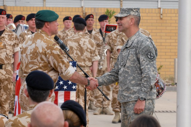 British Maj. Gen. Andy Salmon, Multi-National Division-Southeast commander, and Maj. Gen. Michael Oates, MND-South commander, shake hands during the transfer of responsibility ceremony, March 31, in Basra, Iraq.