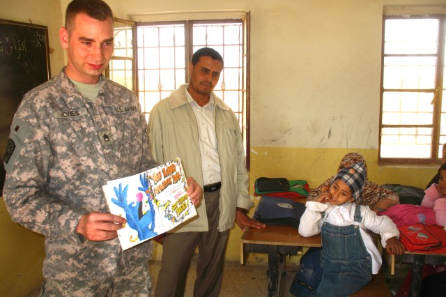 "287th Sustainment Brigade Special Troops Battalion Assistant Operations Noncommissioned Officer Staff Sgt. Lance Jones shows pages from a storybook during a visit as part of the ""Read Iraq"" program at Al Habib School on March 3."