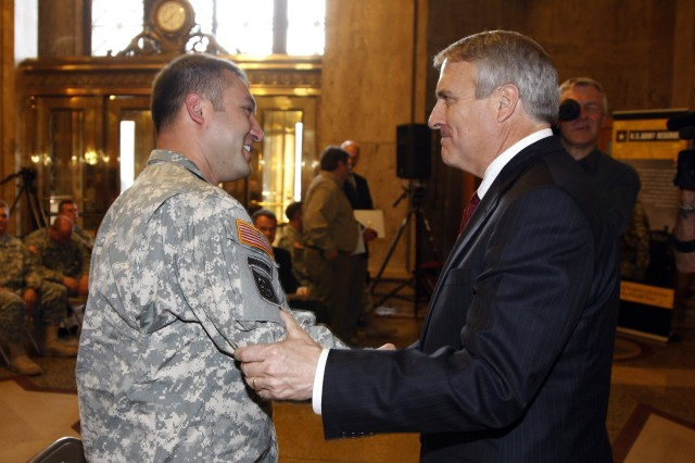 Army Reserve Sgt. Gregory S. Ruske, who earned the Silver Star medal for gallantry in Afghanistan, shakes hands with Colorado Gov. Bill Ritter Jr. in Denver, March 20.