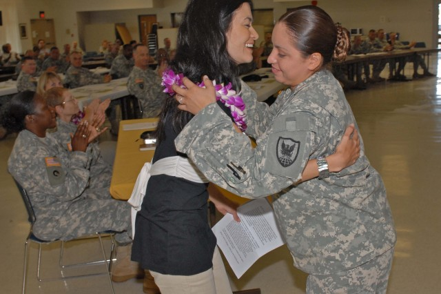 "FORT SHAFTER, Hawaii - A Soldier from the 311th Theater Signal Command welcomes Leilani Munter, guest speaker for the annual Women's History Month observation, with a Lei. This year's theme was ""Women taking the lead to save our planet."" Munter, a NASCAR driver and environmentalist, spoke to Soldiers and Dept. of the Army civilians about the struggles of becoming a professional racecar driver and her many environmental efforts."