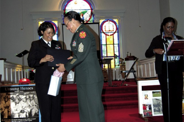 "Senior Chief Petty Officer Fredda Bryan, president, Hampton Roads Chapter of the National Association of Black Military Women,   presents Fort Eustis Garrision Command Sgt. Maj. Carolyn Johnson with a gift of appreciation for her military service during the organization's ""Nothing More to Prove"" event in observance of Women's History Month Saturday at St. Paul Methodist Church in Chesapeake. NABMW is an association of women veterans or active-duty  service members. The group  was founded  in Hampton in 1976 by women who served in the Women's Army Auxiliary Corps and Women's Army Corps during World War II and the Korean and Vietnam Wars."