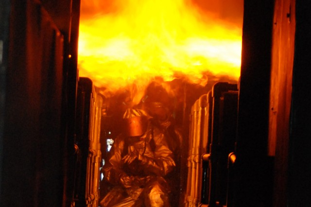 As the handlineman, Senior Airman Bradley Fear leads the charge against a fuselage engulfed in flames. Fear and other members of the 309th Airlift Squadron trained on the simulator at the Woensdrecht Firefighting Training Facility in the Netherlands.