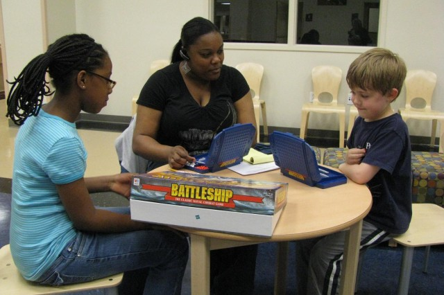 Chelsy Robinson, 9, and Matthew Snyder, 7, take up the challenge of trying to find battleships set up by School Age Services employee Laquita Payne. Several tables and chairs are set up in the atrium of the new School Age Services Center so that children can play games and hang out together.